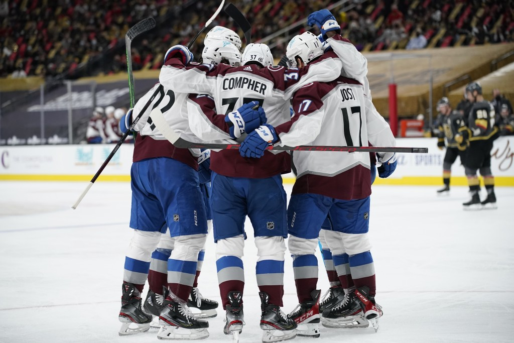 Colorado Avalanche celebrate after left wing J.T. Compher (37) scored against the Vegas Golden Knights during the third period of an NHL hockey game M...