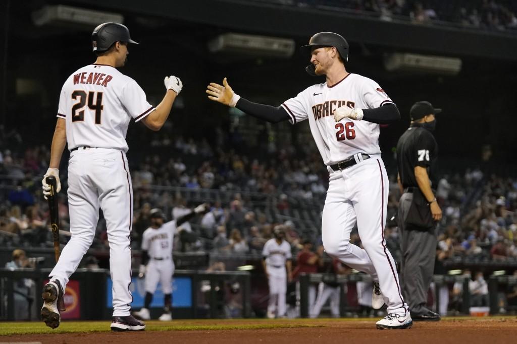 Arizona Diamondbacks' Pavin Smith (26) and Luke Weaver (24) celebrate their runs scored against the Miami Marlins during the third inning of a basebal...