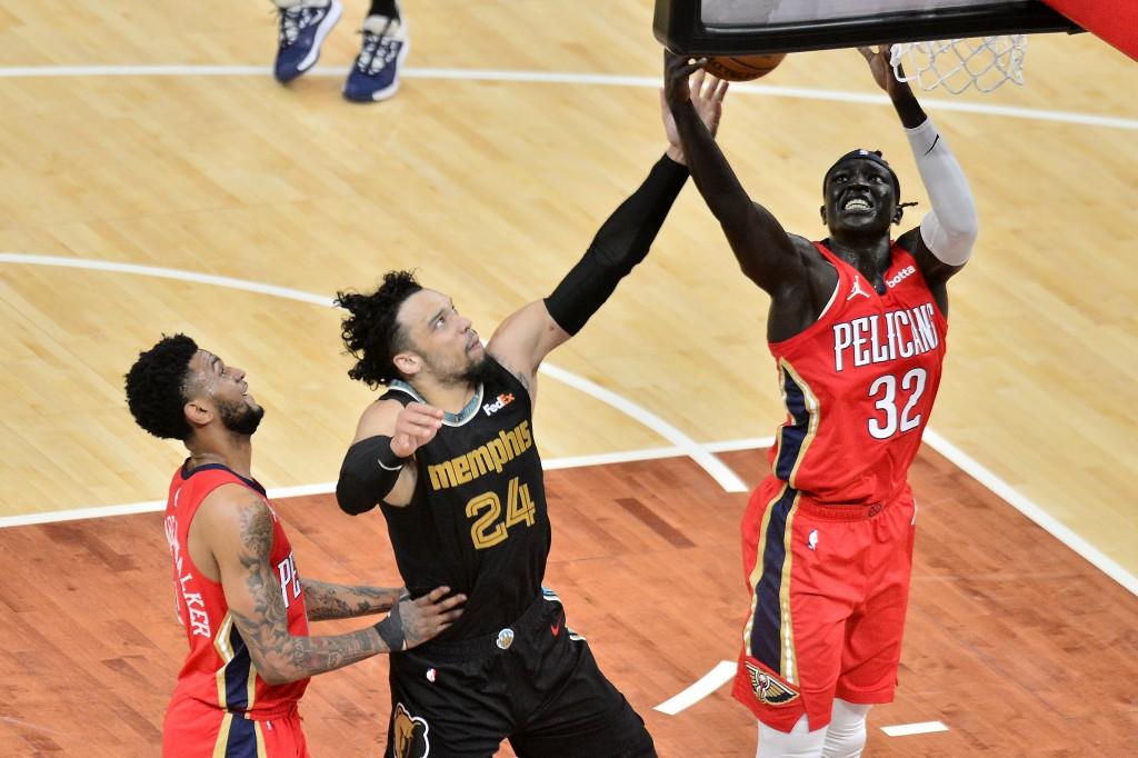 New Orleans Pelicans forward Wenyen Gabriel, right, and Memphis Grizzlies forward Dillon Brooks, center, reach for the ball as guard Nickeil Alexander...