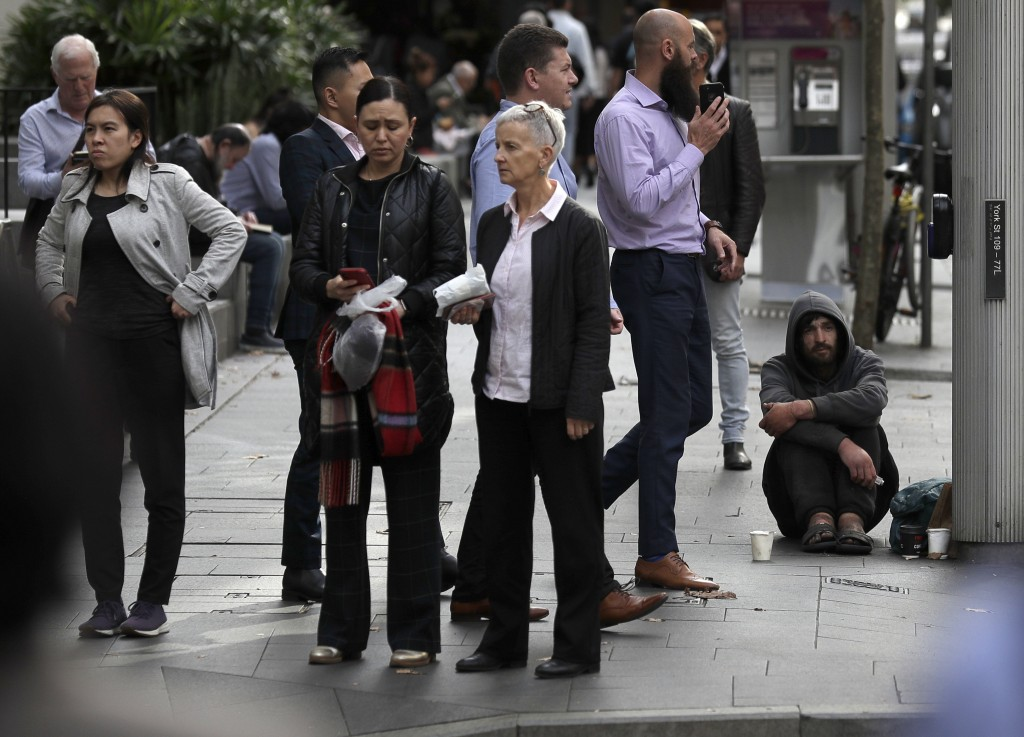 A man, at right, panhandles for money on a corner in Sydney, Tuesday, May 11, 2021, as the government prepares to release its big-spending economic pl...