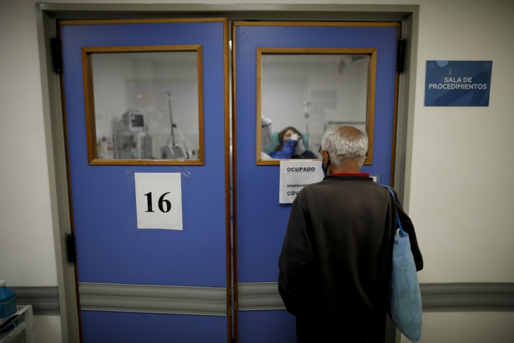 A man watches his wife who is suspected of having COVID-19 as she is attended at Llavallol Dr. Norberto Raúl Piacentini Hospital in Lomas de Zamora, A...