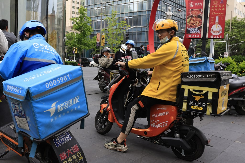FILE - In this April 21, 2021, file photo, a Meituan delivery man in yellow goes on his rounds in Shanghai. Shares in Meituan, China's largest food de...