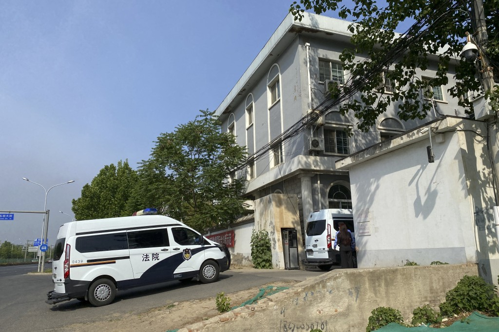 Court police vans move into a courthouse in Beijing, Tuesday, May 11, 2021. Two amateur computer coders taken by police from their Beijing homes last ...