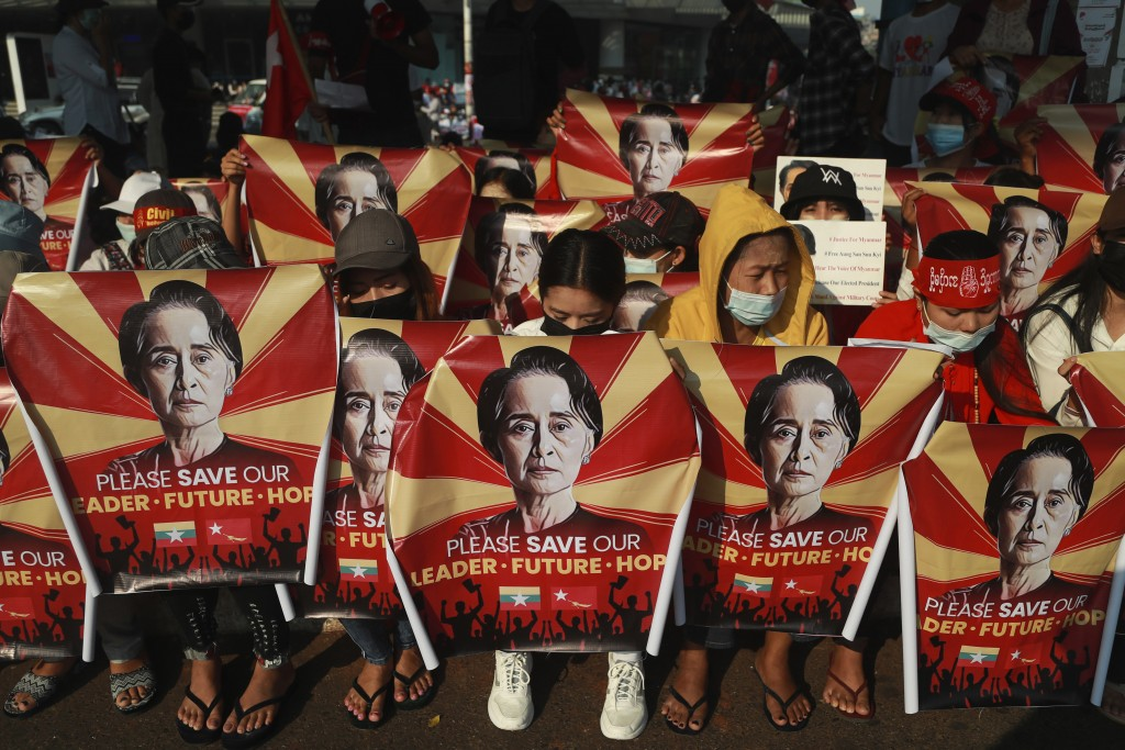 FILE - In this Feb. 20, 2021, file photo, anti-coup protesters hold identical posters with an image of deposed Myanmar leader Aung San Suu Kyi as they...