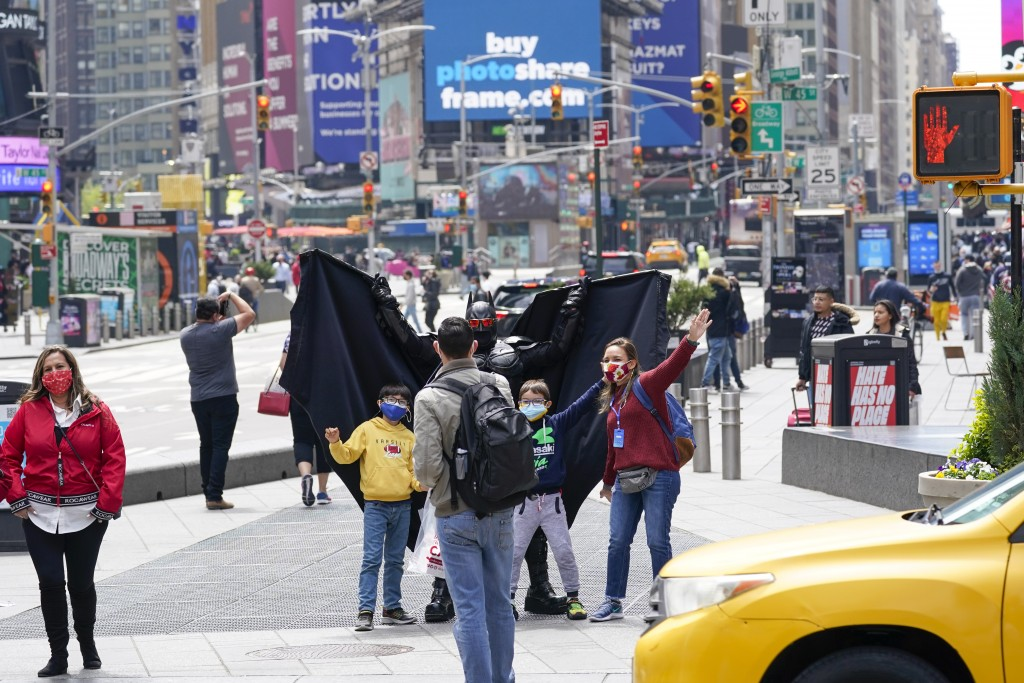 Visitors to New York's Time Square pose for a photo with a street performer working for tips dressed as Batman, Tuesday, April 27, 2021. In recent wee...