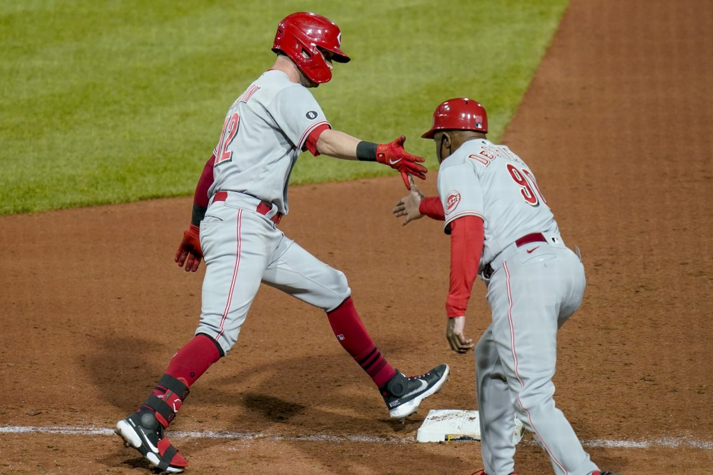 Cincinnati Reds' Tyler Naquin (12) is greeted by first base coach Delino DeShields as he rounds the bases after hitting a three-run home run against t...