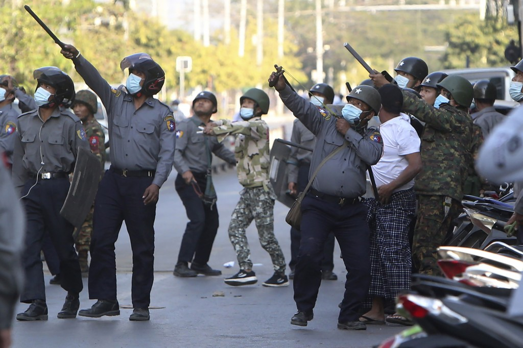 FILE - In this Feb. 15, 2021, file photo, a police officer aims a slingshot towards an unknown target during a crackdown on anti-coup protesters holdi...