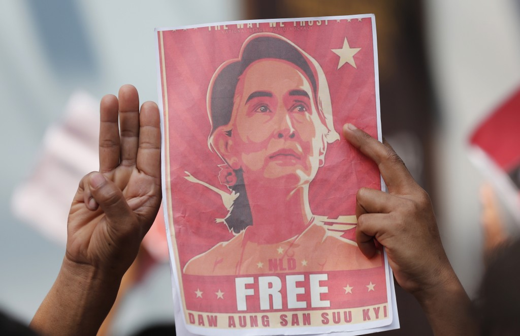 FILE - In this Feb. 8, 2021, file photo, Myanmar nationals living in Thailand hold pictures of Myanmar leader Aung San Suu Kyi gesture with a three-fi...
