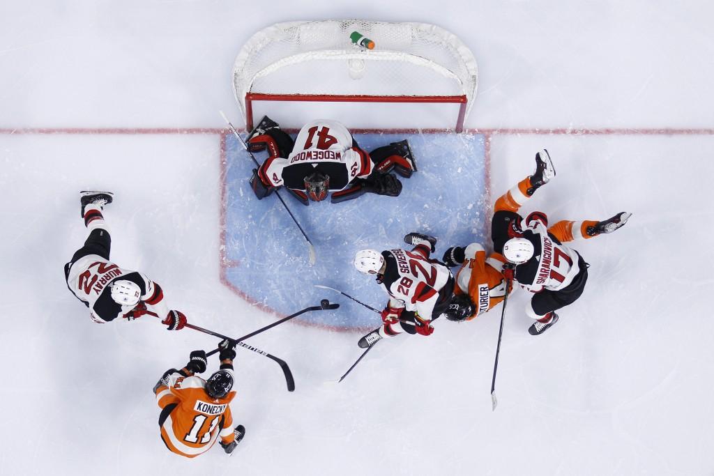 Philadelphia Flyers' Travis Konecny (11) tries to get a shot past New Jersey Devils' Scott Wedgewood (41), Ryan Murray (22) and Damon Severson (28) as...