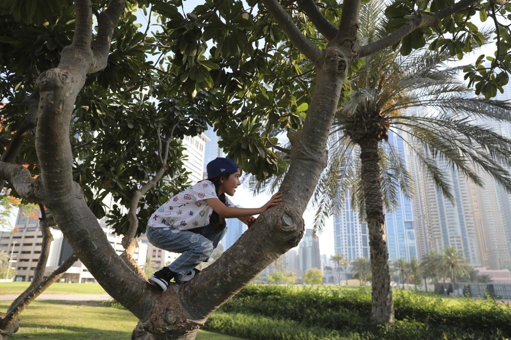 Michelle Rasul climbs a tree at a park near her house in Dubai, United Arab Emirates, Sunday, May 9, 2021. Rasul, a 9-year-old girl from Azerbaijan wh...