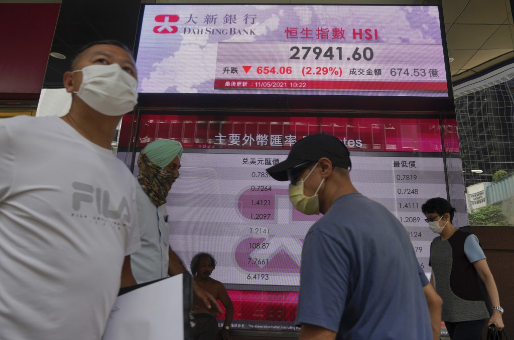 People walk past a bank's electronic board showing the Hong Kong share index at Hong Kong Stock Exchange Tuesday, May 11, 2021. Shares dropped Tuesday...
