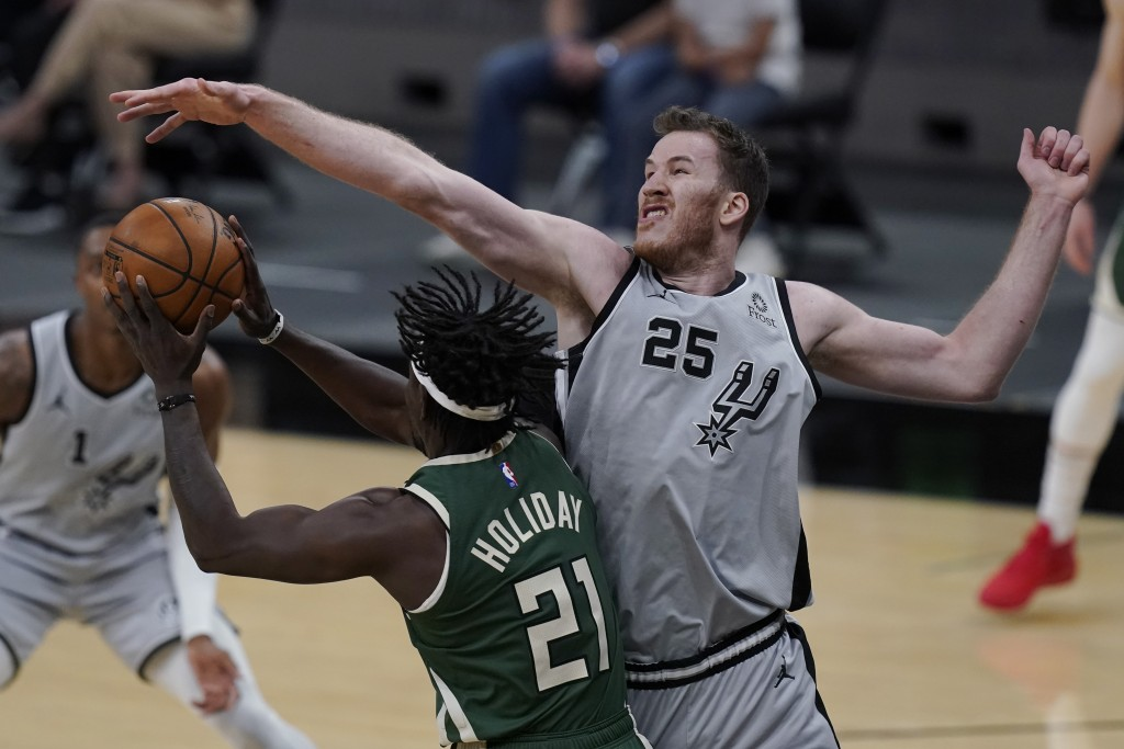 Milwaukee Bucks guard Jrue Holiday (21) is defended by San Antonio Spurs center Jakob Poeltl (25) during the first half of an NBA basketball game in S...