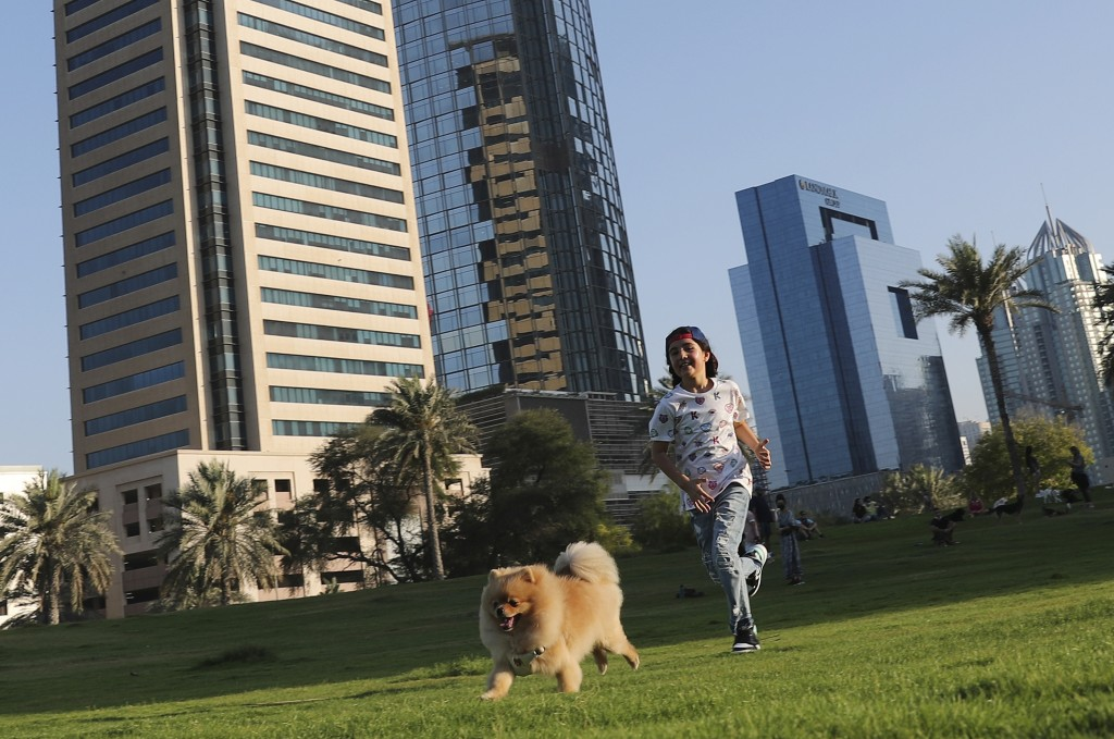 Michelle Rasul chases a friend's dog at a park near her house in Dubai, United Arab Emirates, Sunday, May 9, 2021. Rasul, a 9-year-old girl from Azerb...