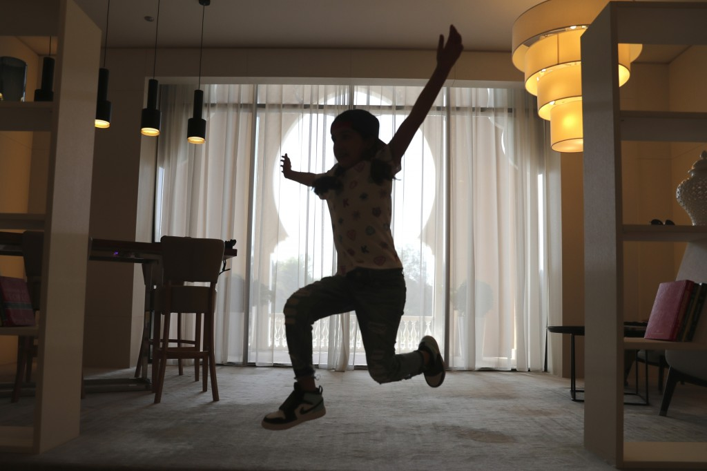 Michelle Rasul jumps around in the lobby of her apartment building in Dubai, United Arab Emirates, Sunday, May 9, 2021. Rasul, a 9-year-old girl from ...