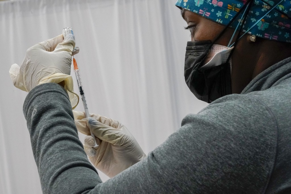 FILE - In this April 8, 2021, file photo, a Northwell Health registered nurse fills a syringe with the Johnson & Johnson COVID-19 vaccine at a pop up ...