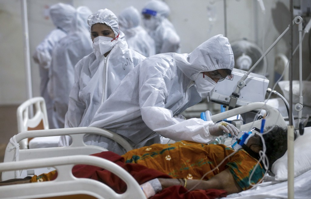 A health worker tries to adjust the oxygen mask of a patient at the BKC jumbo field hospital, one of the largest COVID-19 facilities in Mumbai, India,...