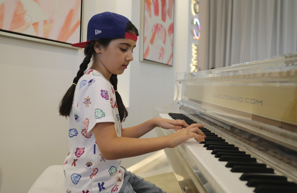 Michelle Rasul plays piano in the lobby of her apartment building in Dubai, United Arab Emirates, Sunday, May 9, 2021. Rasul, a 9-year-old girl from A...