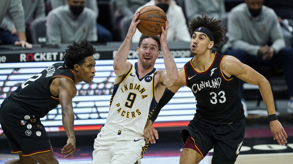 Indiana Pacers' T.J. McConnell (9) drives between Cleveland Cavaliers' Collin Sexton (2) and Brodric Thomas (33) in the second half of an NBA basketba...