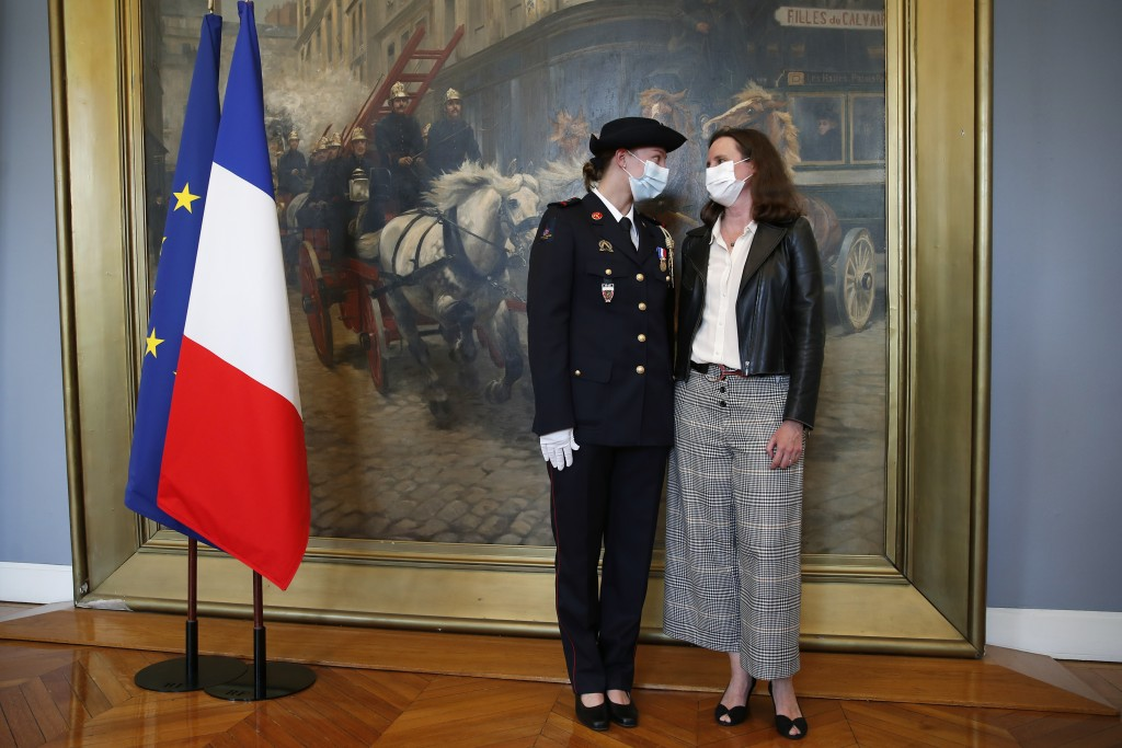 French math teacher-volunteer fighter, Marion Dehecq, left, poses with Paris-based Associated Press journalist Lori Hinnant, after she receives a bron...