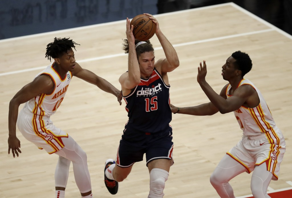 Washington Wizards' Robin Lopez, center, drives the ball between Atlanta Hawks' De'Andre Hunter, left, and Onyeka Okongwu, right, during the first hal...