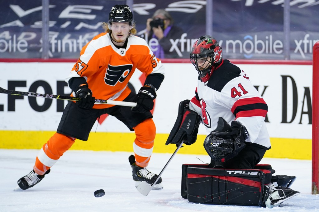 New Jersey Devils' Scott Wedgewood, right, blocks a shot as Philadelphia Flyers' Wade Allison looks for the rebound during the second period of an NHL...