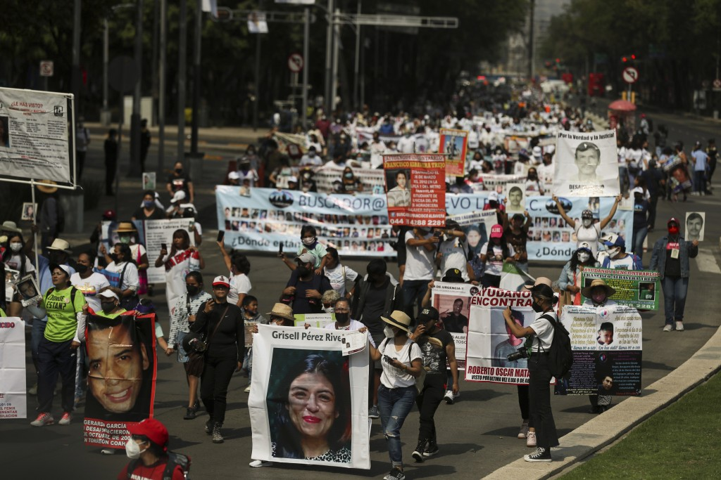 People carry photographs during a march in remembrance of those who have disappeared, on Mother's Day in Mexico City, Monday, May 10, 2021. (AP Photo/...