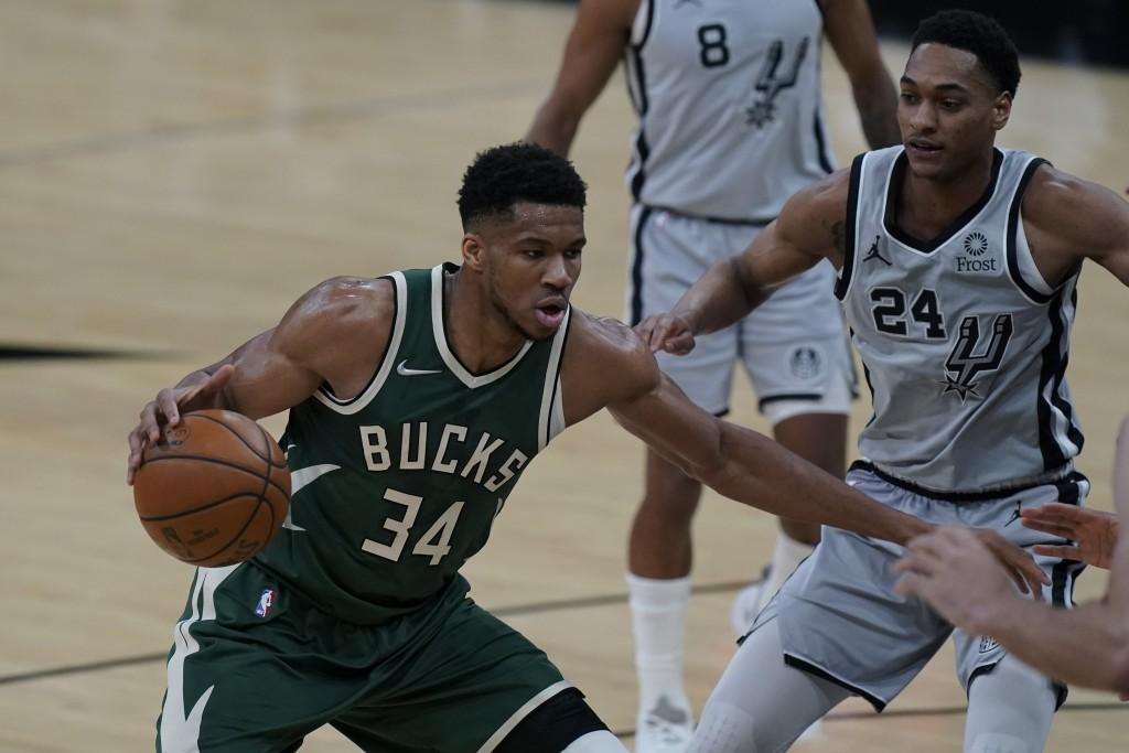 Milwaukee Bucks forward Giannis Antetokounmpo (34) drives around San Antonio Spurs guard Devin Vassell (24) during the first half of an NBA basketball...