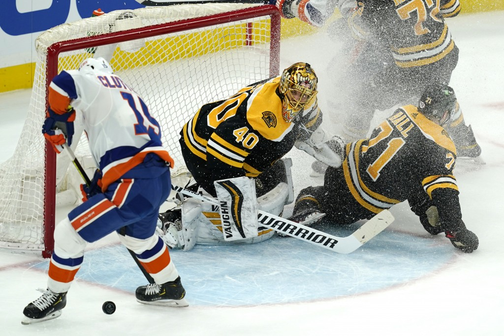 New York Islanders right wing Cal Clutterbuck, left, can't control the puck to get a shot off as Boston Bruins goaltender Tuukka Rask, center, and Bru...
