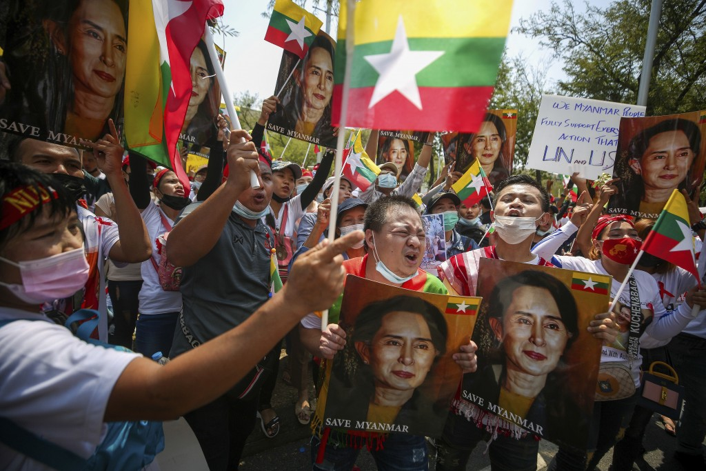 FILE - In this March 7, 2021, file photo, Myanmar nationals living in Thailand hold pictures of deposed Myanmar leader Aung San Suu Kyi as they protes...