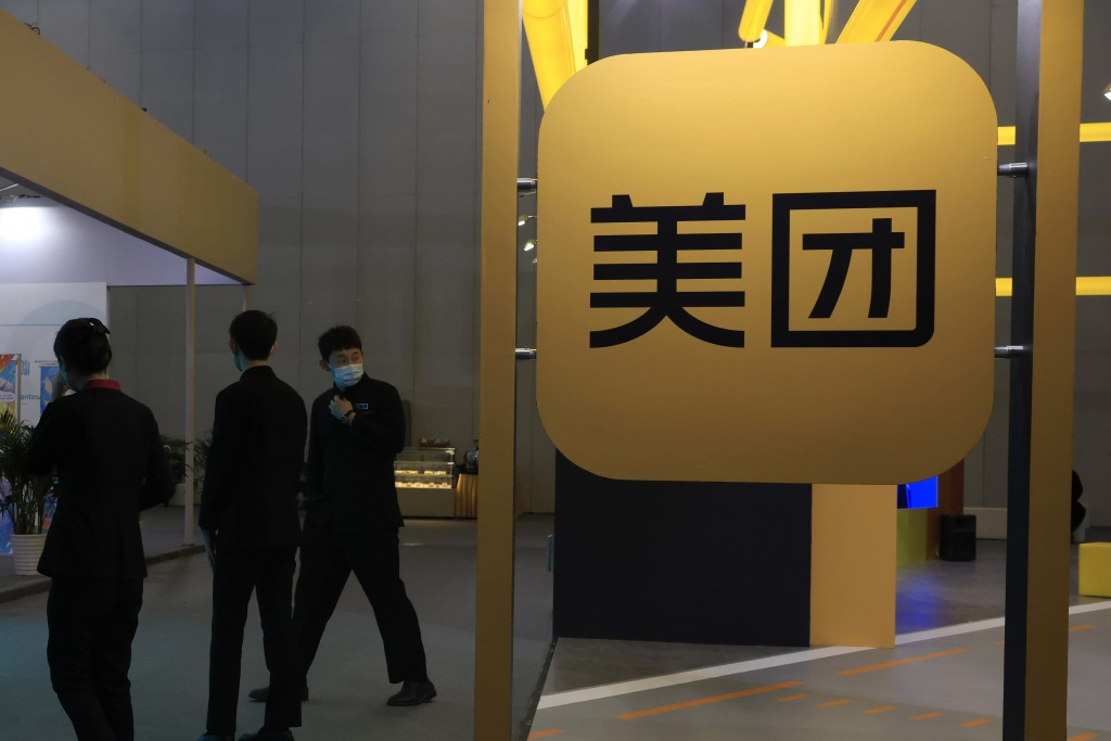 FILE - In this April 30, 2021, file photo, workers walk by the logo of Meituan during an Internet Technology Expo in Beijing. Shares in Meituan, China...