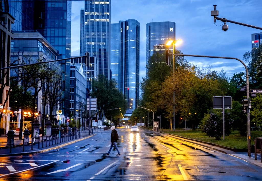 A man crosses a street shortly after the end of the curfew in central Frankfurt, Germany, Tuesday, May 11, 2021. (AP Photo/Michael Probst)