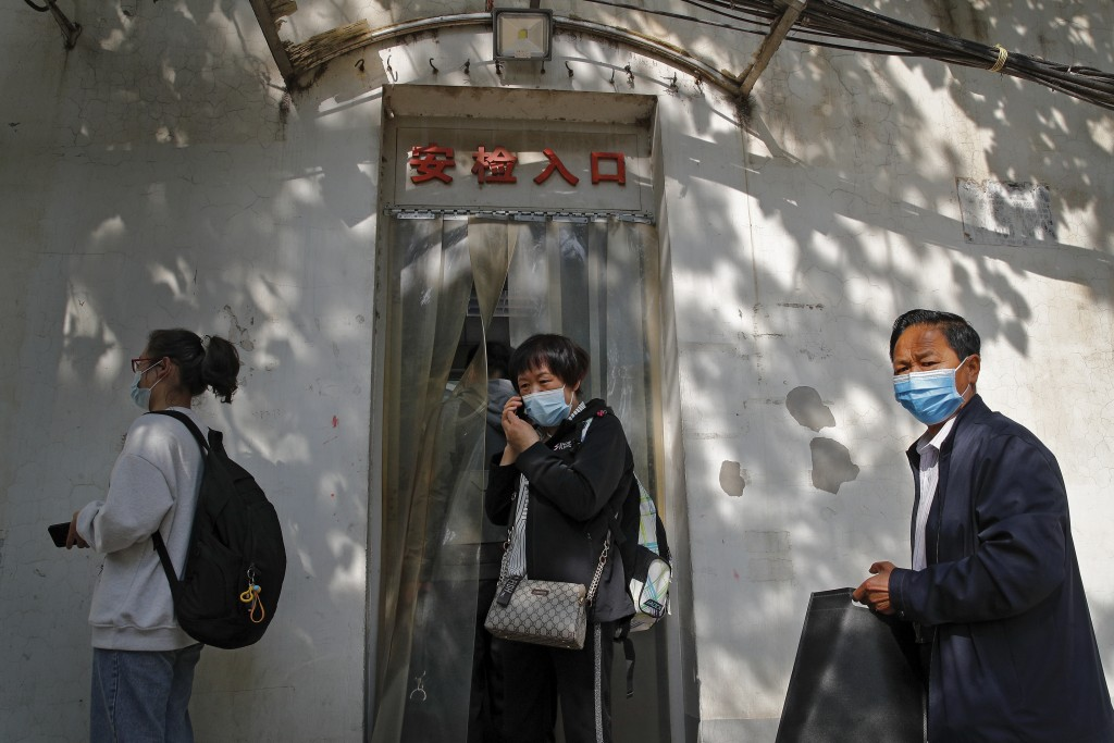 Wei Xiuwen, mother of Chen Mei, center, talks on phone as she prepares to enter a courthouse to attend her child's court case in Beijing, Tuesday, May...