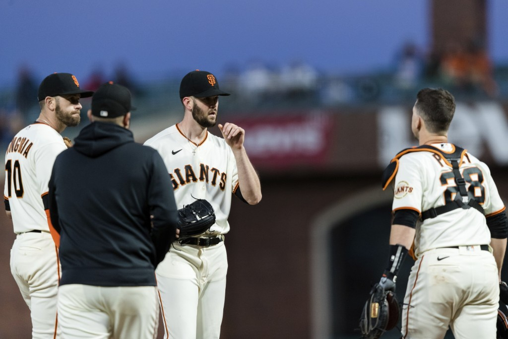 San Francisco Giants starter Alex Wood, center, talks to teammates Buster Posey (28) and Evan Longoria (10) and pitching coach Andrew Bailey, second f...