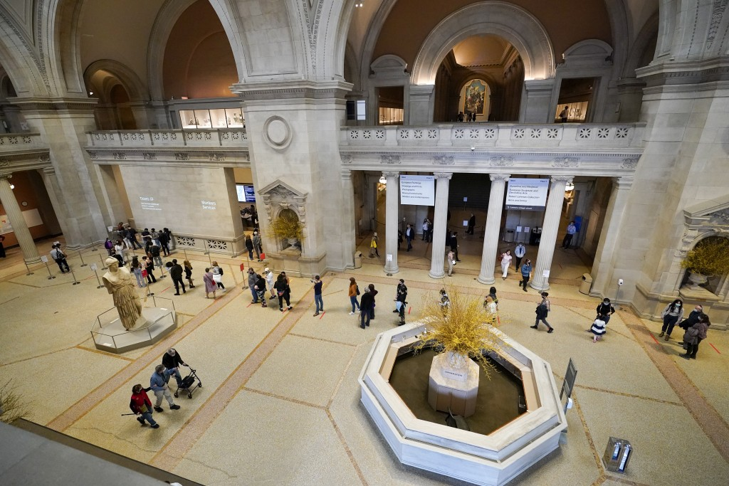 Visitors to the Metropolitan Museum of Art stand in line to purchase tickets, Thursday, April 29, 2021, in New York. In recent weeks, tourism indicato...