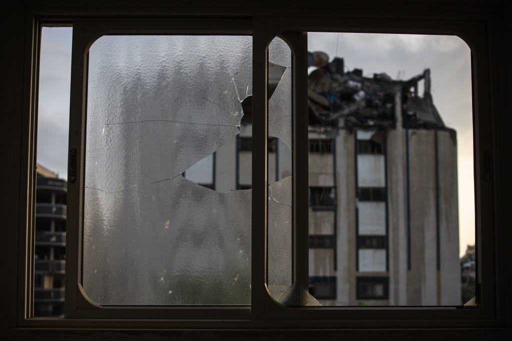 A destroyed rooftop of a residential building hit by Israeli missile strikes is seen through a broken window at the Shati refugee camp in Gaza City, e...