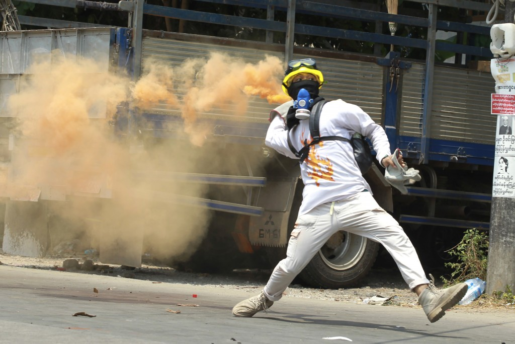 FILE - In this March 27, 2021, file photo, an anti-coup protester throws a smoke bomb against police crackdown in Thaketa township Yangon, Myanmar. Th...