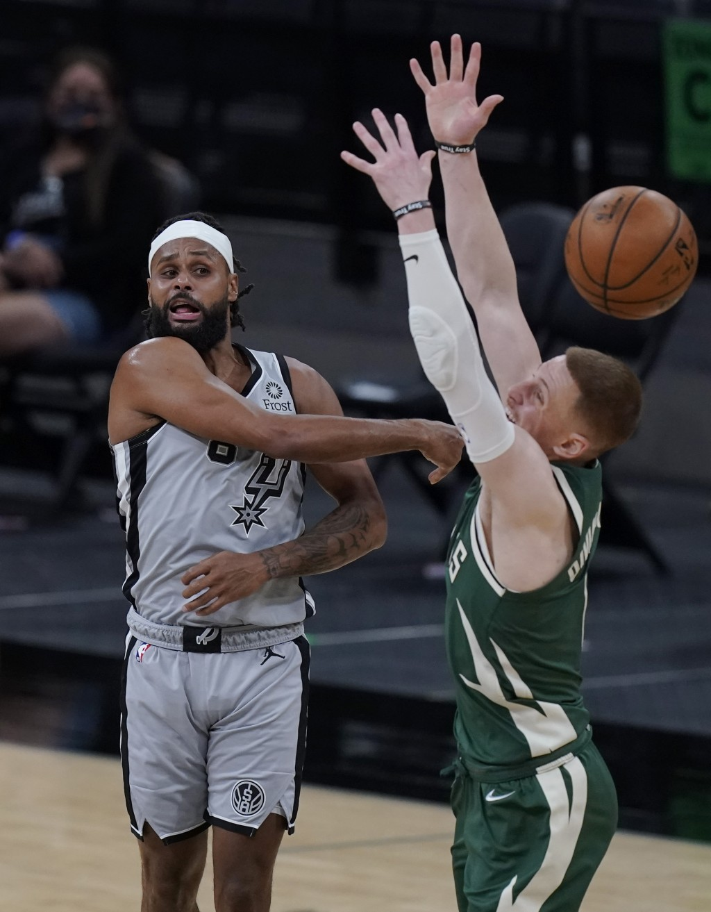 San Antonio Spurs guard Patty Mills, left, passes the ball over Milwaukee Bucks guard Donte DiVincenzo (0) during the second half of an NBA basketball...