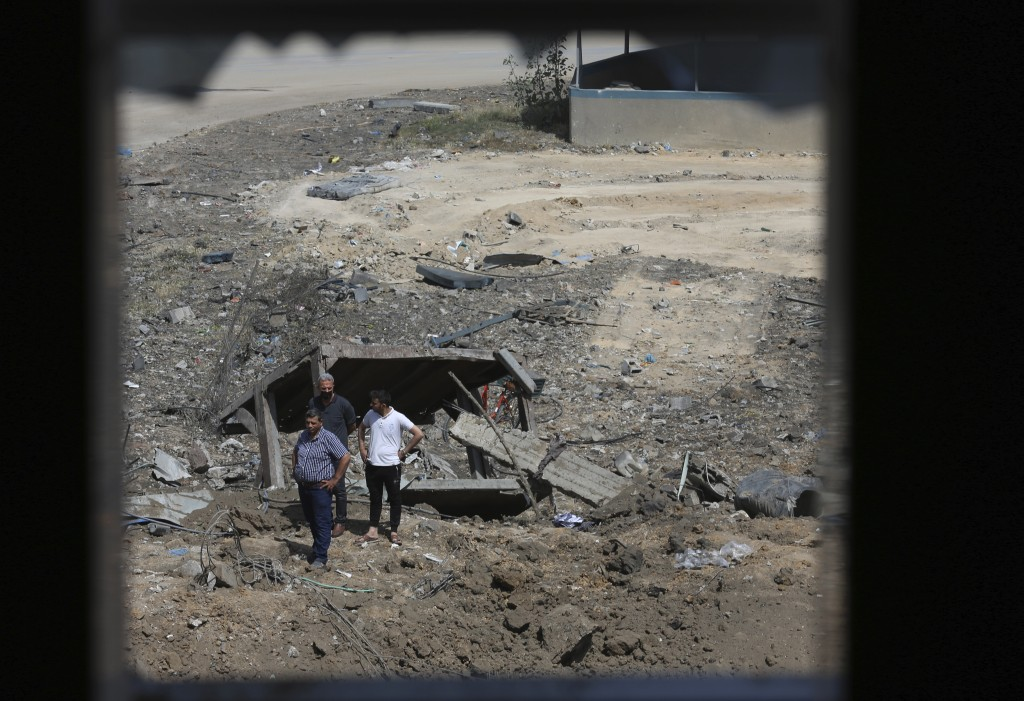 Palestinians inspect the rubble of Ice factory and mechanic garages destroyed by Israeli airstrikes, in Gaza City, Tuesday, May 11, 2021. (AP Photo/Ad...