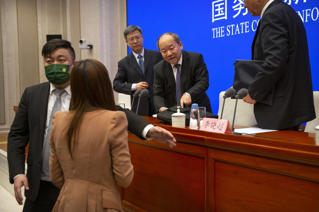 Ning Jizhe, center, commissioner of China's National Bureau of Statistics, listens to a journalist's question after a press conference at the State Co...