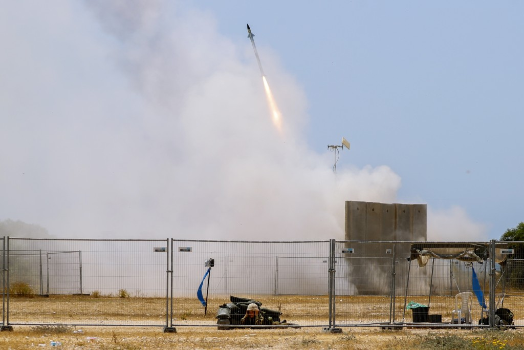 A Israeli soldier takes cover as an Iron Dome air defense system launches to intercept a rocket from the Gaza Strip, in Ashkelon, southern Israel, Tue...