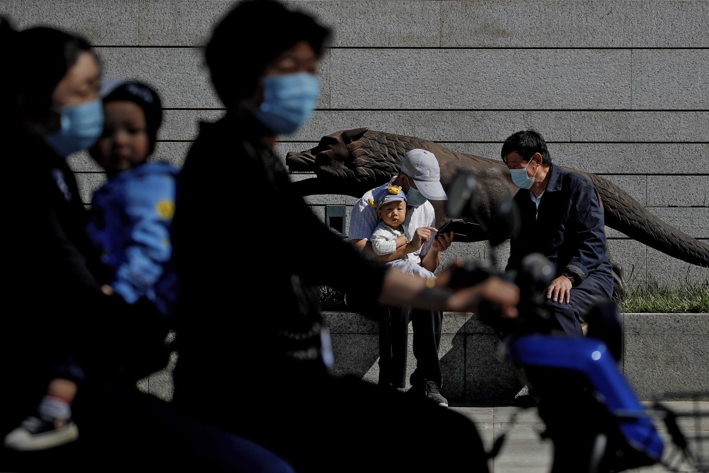 A couple wearing face masks and a child on an electric-powered scooter pass by a man holding an infant as he chats with another man near a sculpture o...