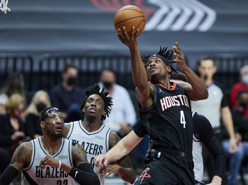Houston Rockets forward Danuel House Jr., right, shoots over Portland Trail Blazers forwards Robert Covington, left, and Nassir Little during the firs...