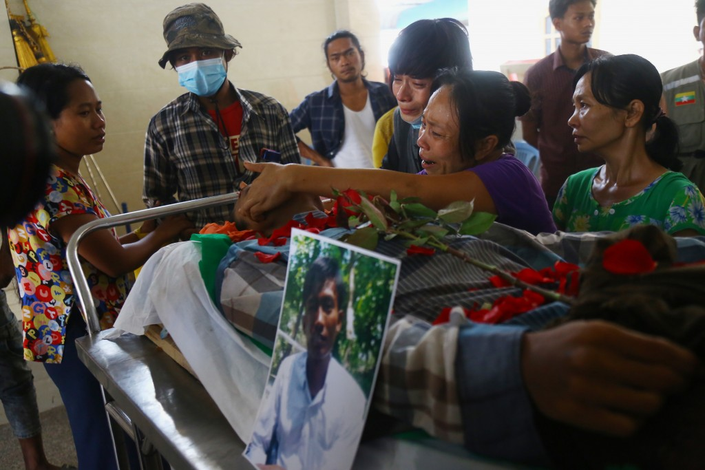 FILE - In this March 30, 2021, file photo, family members mourn over Aung Myo Thant who was killed during clashes with police in Yangon, Myanmar. The ...