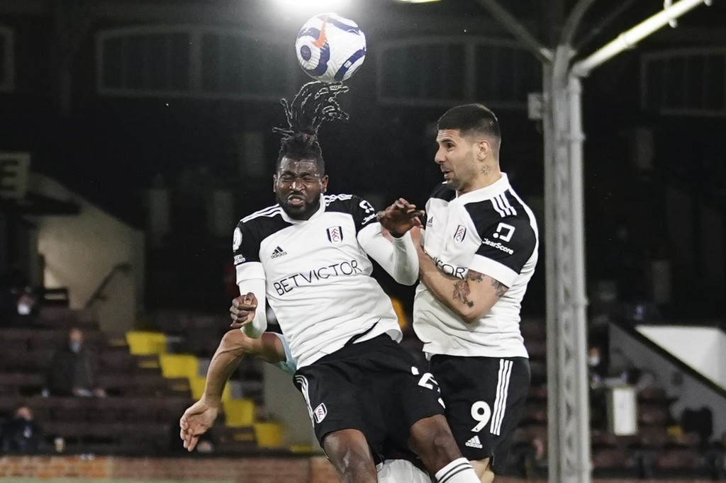 Fulham's Andre-Frank Zambo Anguissa, left, and Fulham's Aleksandar Mitrovic jump for a header during the English Premier League soccer match between F...