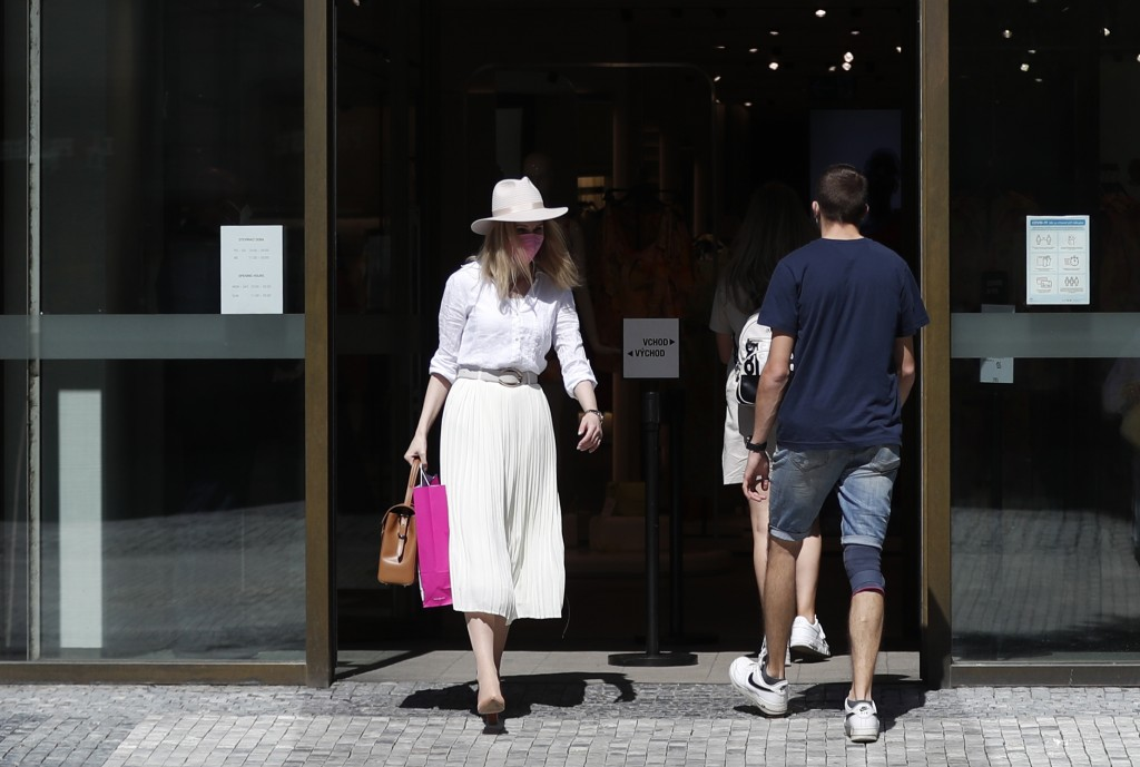 A woman walks out of a shop in Prague, Czech Republic, Monday, May 10, 2021. The Czech Republic is massively relaxing its coronavirus restrictions as ...