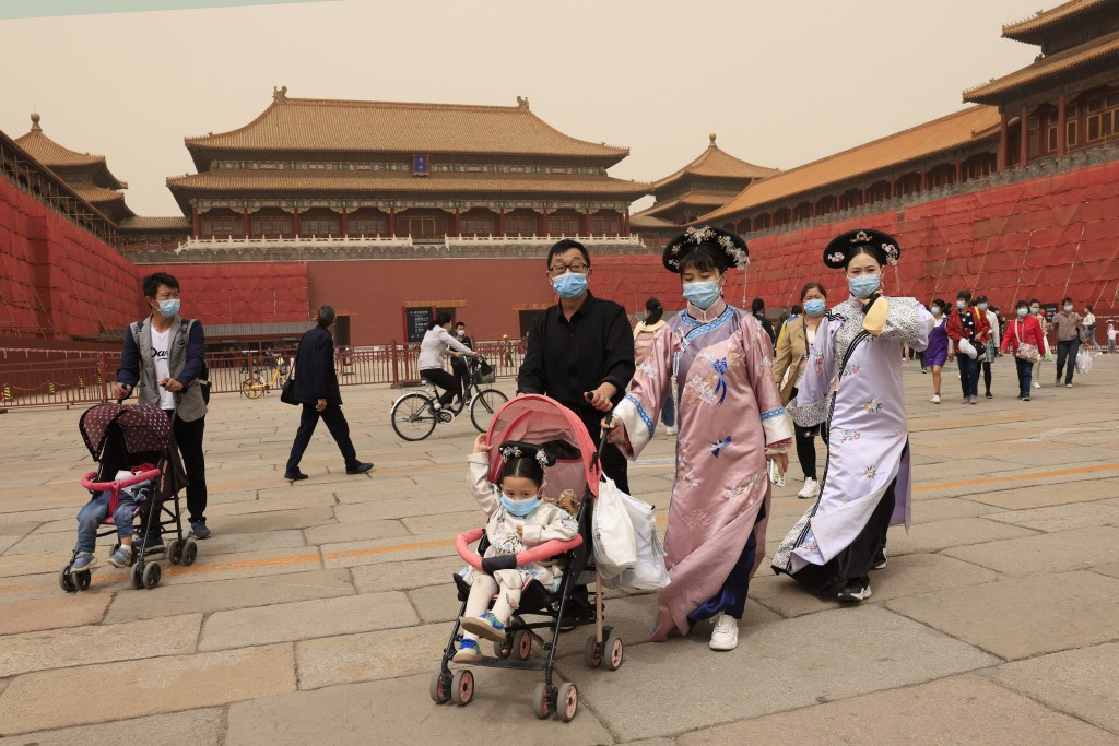 Residents dressed in traditional costumes visit the Forbidden City in Beijing on May 6, 2021.  China's population growth is falling closer to zero as ...