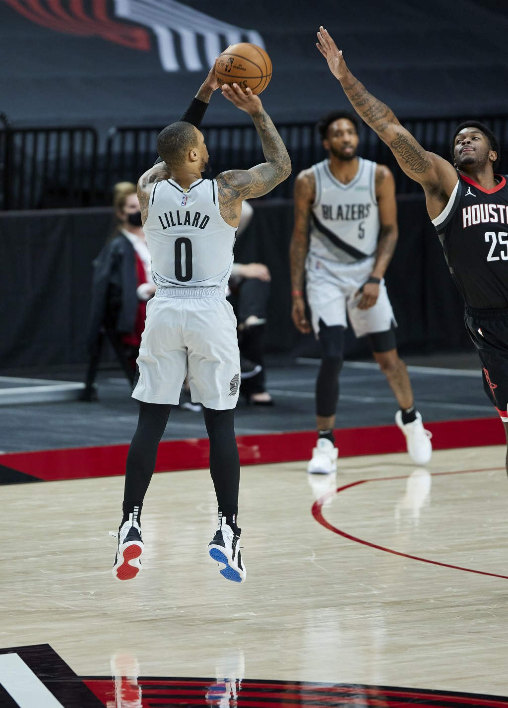 Portland Trail Blazers guard Damian Lillard, left, shoots a 3-point basket over Houston Rockets forward Cameron Oliver during the first half of an NBA...