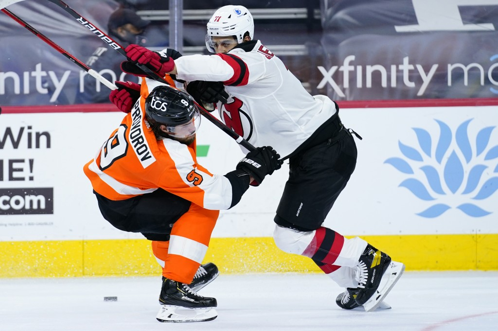 Philadelphia Flyers' Ivan Provorov, left, and New Jersey Devils' Jonas Siegenthaler battle for the puck during the second period of an NHL hockey game...