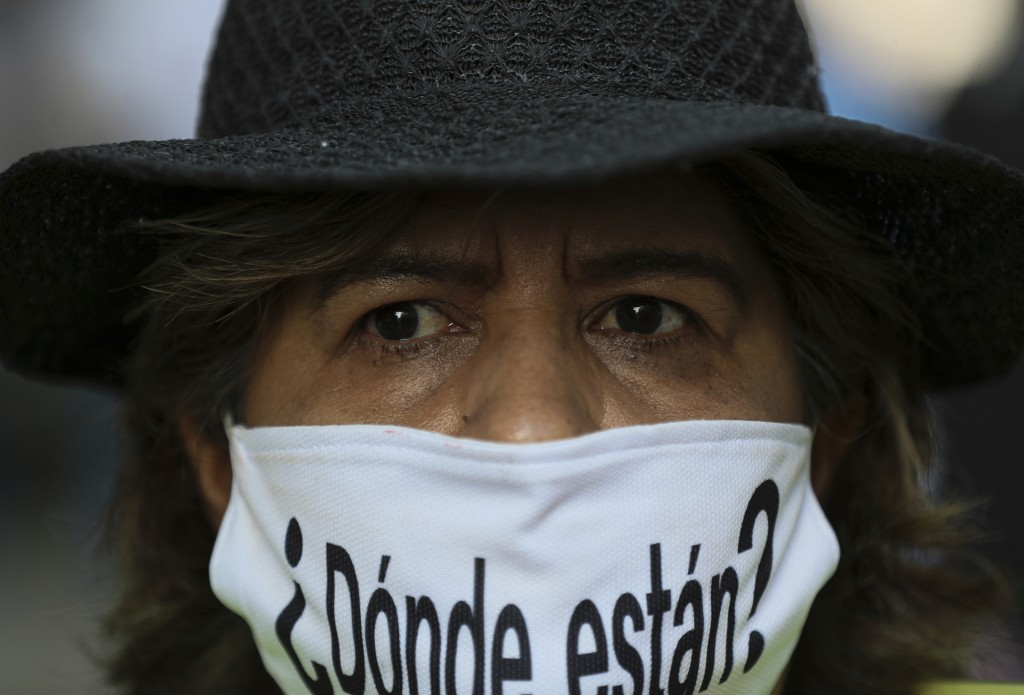 """A person wears a mask with the Spanish question: """"Where are they?"""" during a march in remembrance of those who have disappeared, on Mother's Day in Mex..."""