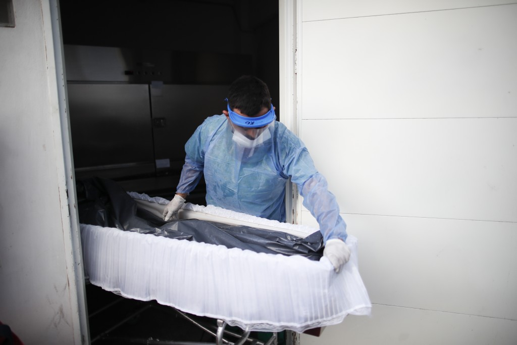 A healthcare worker pushes a coffin with the remains of a patient who died from COVID-19 at Llavallol Dr. Norberto Raúl Piacentini Hospital in Lomas d...